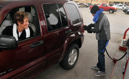 """Tribune-Star/Joseph C. Garza<br /> Kidding """"The Kidd"""": Connie Huff jokes with her grandson, 100.7 MIX FM's Jimmie Kidd, as he pumps her gas as part of United Day for the United Way Friday at Baesler's Market."""