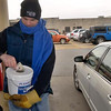 Tribune-Star/Joseph C. Garza<br /> Something extra for a good cause: City councilman Neil Garrison inserts a donation from a customer at the Baesler's Market gas pumps into a collection bucket Friday during the United Day for the United Way.