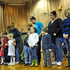 Proud: Participants in continuing education and their children line up for a photo at the end of Friday's assembly at Deming Elementary School.