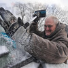 Tribune-Star/Jim Avelis<br /> Icy start: Stuart McCain scrapes ice from his windshield Saturday morning before making a service call for Line of Sight Satellite.