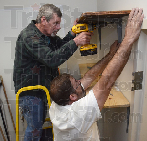 Tribune-Star/Jim Avelis<br /> Progress: Mike Fagg and Steve Harvey work together to install shelves in the cleaning room of the wellness Clinic now under construction in the Vigo County government building.