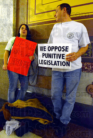 """Everywhere a sign: Elizabeth Glosser and Shawn Hurt of Ft. Branch hold signs stating their view of """"Right to Work"""" while waiting the Indiana statehouse."""