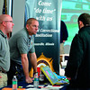 Tribune-Star/Joseph C. Garza<br /> Recruiting professionals: Greg Zykan and Kurt Neudeck, recruiters for the Greenville, Ill., Federal Correctional Institution, talk to job seekers at the Federal Correctional Complex job fair Monday.