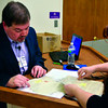 Tribune-Star/Joseph C. Garza<br /> What could they be?: Tim Phipps looks over documents from 1860 to 1940 for Jenny Ingram during a break from his presentation Monday at the Vigo County Public Library.