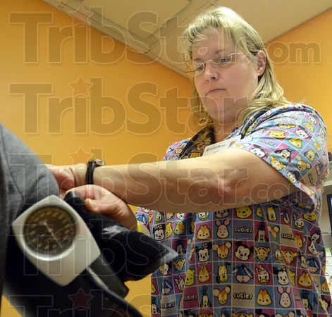 Pressure check: LPN Tammi Howard attaches a blood pressure monitor to a patient during her shift at the Vermillion-Parke Health facility.