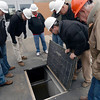 Tribune-Star/Joseph C. Garza<br /> Where it flows: Troy Swan, second from right, a water services engineer with HNTB, pulls back a panel to show a tour group where waste enters the Terre Haute Wastewater Utility's new headworks building Tuesday.