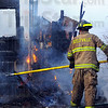 Tribune-Star/Jim Avelis<br /> Fire fighter: Seelyville volunteer firefighter Joe Stewart uses a pike pole to pull shingles from the house on South Main Street in Seelyville. An explosion and fire Tuesday afternoon destroyed the dwelling.