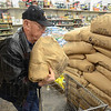 Tribune-Star/Jim Avelis<br /> Regular visit: Bill Cardwell loads another bag of nyger seed into his shopping cart at Rural King Tuesday afternoon. This bag makes 300 pounds of seed he has bought so far this winter to keep his five finch feeders filled.