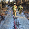 Tribune-Star/Jim Avelis<br /> Long walk: The house fire in Seelyville was located well east of Main Street up a gravel driveway. Water supply hoses run up to a pumper truck that provided pressure for the fire hoses.