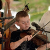 "Tribune-Star/Joseph C. Garza<br /> Blueberry pickers: Eli Taylor plays his part of ""Nine Pound Hammer"" during the Coon Holler Kids' performance at the Terre Foods Blueberry Festival Thursday at Central Presbyterian Church."
