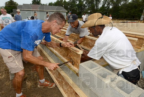 Tribune-Star/Joseph C. Garza<br /> Teamwork: Habitat for Humanity volunteers John Pommier, chairperson for the Indiana State University Department of Kinesiology, Recreation, and Sport and Cleveland Brown work together to hammer a beam in place for a new home near the corner of Chase and 23rd Streets Thursday.