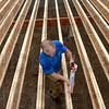 Tribune-Star/Joseph C. Garza<br /> Sticky situation: Indiana State University student and volunteer Joseph Jones of Lafayette lays down subfloor adhesive as he and his fellow Habitat for Humanity volunteers build a home near the corner of 23rd and Chase Streets Thursday.