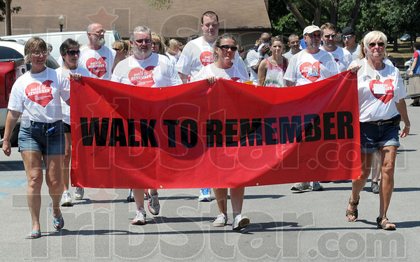 Walk: Walk to Remember participants carry a banner as they walk through Deming Park during Sunday's event.