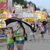 Prepared: Julie McCammon and her daughter Annabelle try to decide what they are going to eat during a light rain Sunday evening as the Vigo County Fair begins its 2012 run.