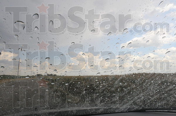 Tribune-Star/Jim Avelis<br /> Little help: Rain drops rest on a windshield with clouds outside. Friday rains were heavy enough to cause a severe thunderstorm warning for areas to the northeast of Terre Haute.