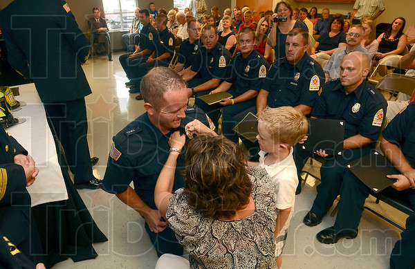 Tribune-Star/Joseph C. Garza<br /> Celebrating with Dad: Six-year-old Lane Sanders helps his mom, Beth Pilarski, pin his dad Bram Sanders' new Terre Haute Fire Department badge on his uniform during a graduation ceremony for the 2012 Firefighter Recruit Class at the new Emergency Responder Training Academy Friday.