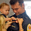 Tribune-Star/Joseph C. Garza<br /> Dad's shiny new badge: 13-month-old Kate Lawson decides to a take a closer look at her dad Scott Lawson's new Terre Haute Fire Department firefighter badge as her mother, Kristy Lawson, tries to pin it on Scott's uniform during a graduation ceremony Friday at the new Emergency Responder Training Academy.
