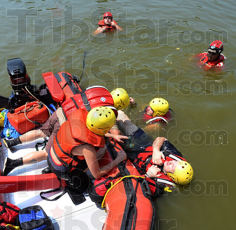 Tribune-Star/Jim Avelis<br /> Roll rescue: Members of the Sugar Creek Fire Department practice water rescue techniques Friday afternoon in the Wabash River. Here Matt Cox is being prepared to be rolled into the inflatable watercraft using straps.