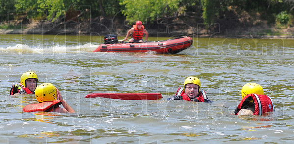 Tribune-Star/Jim Avelis<br /> Realism: Sugar Creek firefighter Josh Milbourn runs his boat around water rescue trainees Matt Adams, Rachel Cary, Matt Cox and Larry Atkinson making waves for them to deal with. The trainees swam across the Wabash River at Fairbanks Park, helping them understand part of the problem in dealing with moving water.