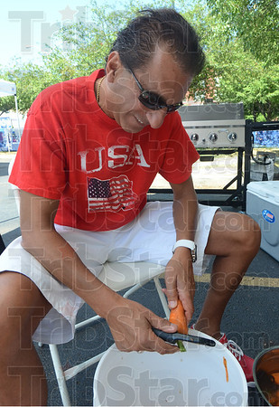 Tribune-Star/Jim Avelis<br /> KP: Vigo County Schools superintendent Dan Tanoos peels carrots in his efforts to help with the Clabber Girl Barbecue competition Saturday.