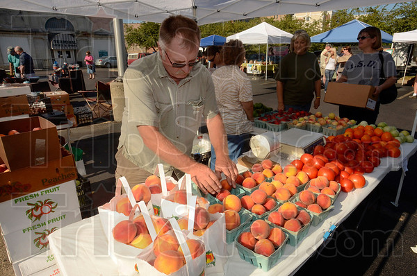 Tribune-Star/Joseph C. Garza<br /> Surviving the drought: Ernie Biltz of Worthington places more peaches out for sale at his stand at Saturday's Farmers Market.