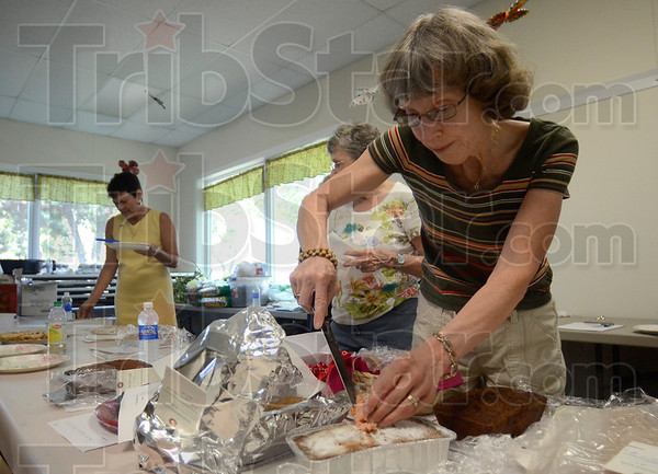 Tribune-Star/Joseph C. Garza<br /> Let's dig in: Bakers' Best judge Jackie Reeves cuts into cherry cake during the judging of baked goods Wednesday at the Wabash Valley Fairgrounds.