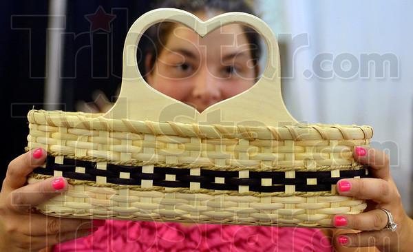Tribune-Star/Joseph C. Garza<br /> From the heart: Michele Stahly displays one of her finished baskets Monday at the Wabash Valley Fairgrounds.