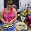 Tribune-Star/Joseph C. Garza<br /> By hand: Michele Stahly builds a basket by hand as she and her mom, Rosa, tend their stand at the Wabash Valley Fairgrounds Monday.