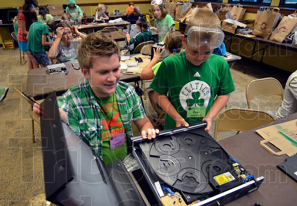 Tribune-Star/Joseph C. Garza<br /> Hands on and brains on learning: Camp Invention counselor Sam Spencer, an Indiana State University student from Brazil, helps Ryan Liebermann, 9, remove the cover of an old DVD player during one of the camp's classes Monday in the Indiana State University campus.