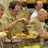 Tribune-Star/Joseph C. Garza<br /> Fruit (or pasta) of their labor: Wabash Valley Correctional Facility inmate James Randle, center, fills his plate with his fellow inmates Monday at the facility near Carlisle. Randle and the others were celebrating the completion of a cooking program by enjoying food they had made themselves.