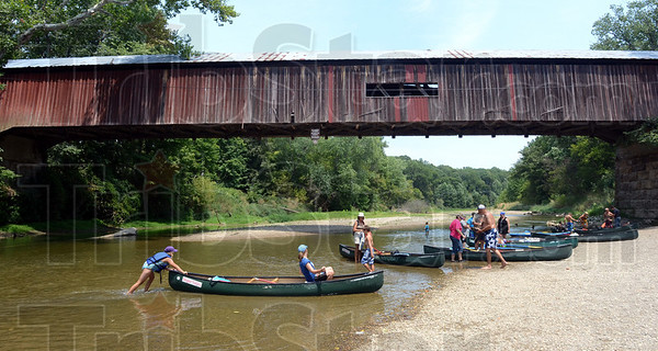 Landing zone: Sugar Creek canoers arrive at their final destination under the Cox Ford Bridge Monday afternoon. Water levels and heat have slowed the normal flow of business.