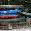 Canoe man: Sugar Valley employee Mark Smith loads canoes from their beaching point at the Cox Ford Bridge Monday afternoon. Water levels have slowed the normal flow of canoers.