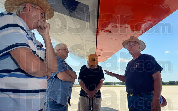 Tribune-Star/Joseph C. Garza<br /> Wing shade history: Gene Christian, right, a crew member of Flagship Detroit, discusses the history of the DC-3 aircraft to visitors of the plane Tuesday at the Terre Haute International Airport-Hulman Field.