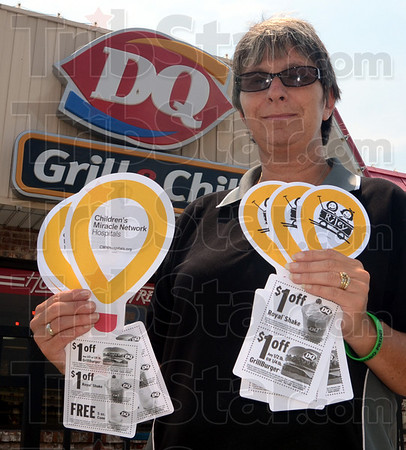 Tribune-Star/Jim Avelis<br /> Helping: Pam Lebrun, manager of the Dairy Queen on Davis Avenue, holds the coupons that will be given out with the purchase of a Blizzard on Thursday.