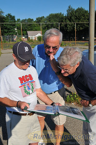 Ed Kozloff of the Motor City Striders shows some 1962 track and field photos to Jim Cleverly (center, Redford High class of '63) and Dick Sharkey.