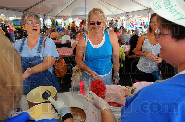 Tribune-Star/Jim Avelis<br /> Smiles are free: Strawberry Festival workers Tammy Morris and Michelle Lewis, in foreground, share a laugh with customers Jenny Large and Annie Lucas. The annual gathering is hosted by the First Congregational Church.