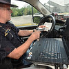 Tribune-Star/Jim Avelis<br /> Checking him out: Indiana State Police trooper Jesse Schmidt scans a motorist's driver's license for a check of other infractions. The man had been clocked at 57 miles per hour in a 45 MPH zone.