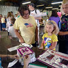 Tribune-Star/Joseph C. Garza<br /> Mini member: Seven-year-old Makenzie Bays, center, enters her project at the Mini-4-H table Saturday morning at the Wabash Valley Fairgrounds. Bays was registering her 4-H projects with the help of her mom, Erin Bays, left, and brother, James Bays, right, as Sarah Puckett accepted her submissions.