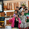 Dedication: Amanda Davis points to a poster of the new stained glass windows during a dedication ceremony at the Central Presbyterian Church Sunday morning. Members of the children's choir observe the event.