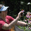 Picture this: Master Gardener Beth Keyes photographs flowers on the property of John Rosene during Satuday's Master Garden Tour.