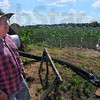 Tribune-Star/Jim Avelis<br /> Extra expense: Bill Lane stands by his irrigation equipment on his farm just south of Rosedale. The system in the background makes a complete pass over the field every 45 hours, spreading about one inch of water in that time.