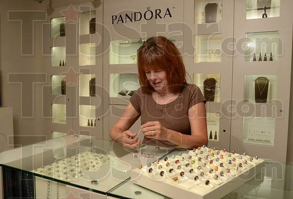 Tribune-Star/Joseph C. Garza<br /> She opened the box: Pandora visual merchandiser Denise Henshaw creates a Pandora bracelet to be put on display during preparation for the grand opening of the new Ross Elliott Jewelers location Friday north of the Honey Creek Mall.