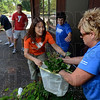 Tribune-Star/Joseph C. Garza<br /> Final touches: Vigo County YMCA Branch Director Eleanor Ramseier holds open a bag for Denise Stone of Terre Haute Savings Bank as Stone and her fellow bank employees clean a patio area Friday.