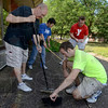 Tribune-Star/Joseph C. Garza<br /> An investment in the community: Terre Haute Savings Bank employees Gary Nees and Brandon Henman sweep up a pile of weeds that were just pulled along with co-workers Laura Griffin and Tyler Fischer Friday at the new Vigo County YMCA. The group was cleaning as part of the United Way Day of Action.