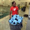 Tribune-Star/Joseph C. Garza<br /> Barbells and a full pool: Vigo County YMCA Aquatic Director LaJoya Smith moves a can of water barbells into a storage closet Friday during final preparations for the opening of the facility.