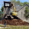 Tribune-Star/Joseph C. Garza<br /> Beginning of a new beginning: Shawn Bell of Bell & Bell uses an excavator to knock down the bell tower of the First Free Will Baptist Church Friday near the intersection of 13th and Franklin Streets.