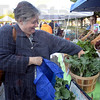 Tribune-Star/Jim Avelis<br /> Early shopper: Gini Banamico selects kale from the baskets of vegetables brought to the downtown farmer's market by the White Violet Center. Tending the booth is Candace Minster.