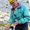 Tribune-Star/Jim Avelis<br /> Busy business: Perry Riley places price stickers on his soap and creams early Saturday at the first outside farmer's market of the summer.