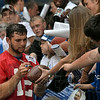 New QB: Indianapolis Colts quarterback Andrew Luck signs a football for a fan after the team's open practice Wednesday at Lucas Oil Stadium in Indianapolis.
