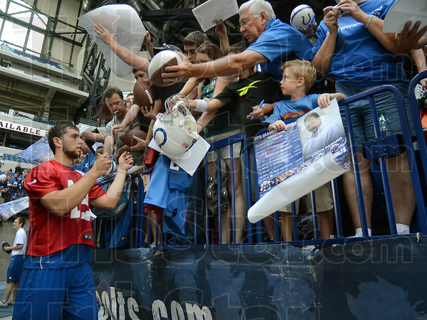Sign line: Indianapolis Colts quarterback Andrew Luck signs autographs for fans after the team's open practice Wednesday at Lucas Oil Stadium in Indianapolis.